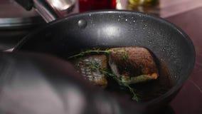Pesce saltato in padella, due pezzi di raccordo loban sulla padella di cottura a vapore video d archivio