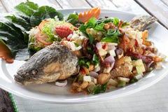 Pesce serpente fritto nel grasso bollente con l'erba tailandese Immagini Stock