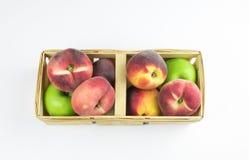 Pesche, albicocche e mele verdi in un canestro di vimini isolatore di frutta su un fondo bianco Primo piano Frutta fresca fotografia stock libera da diritti