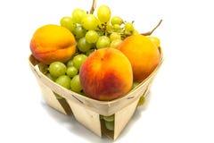 Pesche ed uva in un canestro isolato su bianco Immagini Stock
