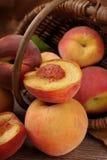 Pesche fresche che cadono da un canestro Fotografie Stock