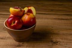 Pesche mature fresche su un piatto marrone, la tavola di legno Immagine Stock Libera da Diritti