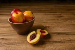 Pesche mature fresche su un piatto marrone, la tavola di legno Fotografie Stock