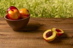 Pesche mature fresche su un piatto marrone, la tavola di legno Immagine Stock