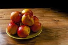 Pesche mature fresche su un piatto verde, la tavola di legno Immagini Stock
