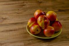 Pesche mature fresche su un piatto verde, la tavola di legno Fotografia Stock Libera da Diritti