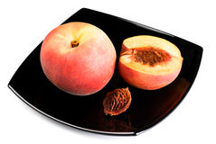 Pesche rosse con il seme sul piatto nero Fotografie Stock