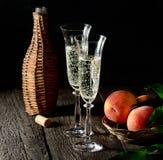 Pesche su un ramo con le foglie in piatti d'annata e due vetri di champagne con il sughero sulla vecchia tavola di legno, stile r Fotografie Stock