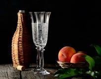 Pesche sul ramo con le foglie in piatto d'annata e due vetri di champagne con sughero sopra la vecchia tavola di legno Stile rust Fotografia Stock