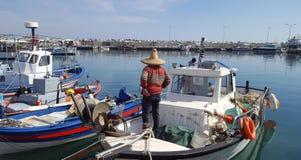 Pescherecci e pescatore nel porto immagine stock