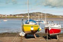 Pescherecci rossi e gialli a bassa marea con le barche nel fondo Immagini Stock Libere da Diritti