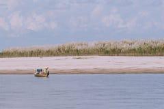 Peschereccio birmano sul fiume con il fondo dell'albero di erba fotografia stock