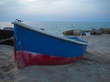 Peschereccio blu rosso sulla sabbia sulla spiaggia fotografia stock