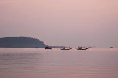 Peschereccio che galleggia nel mare all'alba Immagine Stock