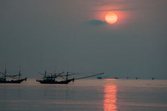 Peschereccio che galleggia nel mare all'alba Immagini Stock