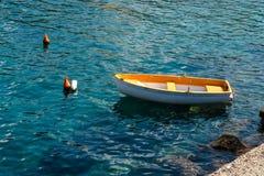 Peschereccio che galleggia sull'acqua, sul mare blu e sul cielo con copyspace fotografie stock