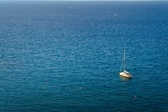 Peschereccio che galleggia sull'acqua, sul mare blu e sul cielo con copyspace immagine stock libera da diritti