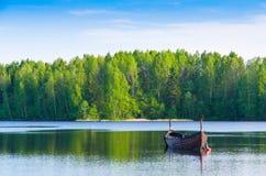 Peschereccio di legno su un lago calmo da un'abetaia Immagini Stock