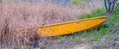 Peschereccio giallo sulla riva in erba alta Immagine Stock
