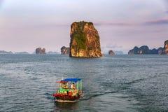 Peschereccio tradizionale nella baia in un tramonto porpora, patrimonio naturale del mondo dell'Unesco, Vietnam di Halong fotografia stock