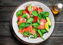 Peschi l'insalata Insalata con le fette di salmone, di pomodori e di spinaci con il succo di cedro immagine stock