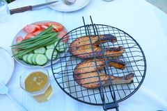Peschi la cottura sul fuoco con i pomodori ed i cetrioli Fotografia Stock