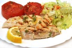 Pesci bianchi e pomodoro cotti con insalata Fotografia Stock