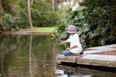 Pesci d'alimentazione della ragazza in un raggruppamento del giardino Fotografie Stock Libere da Diritti