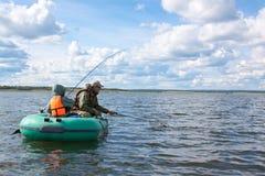 Pesci del figlio e del padre in barca Fotografie Stock