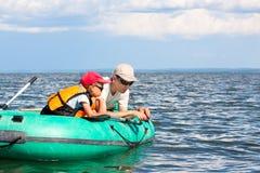 Pesci del figlio e del padre in una barca Immagini Stock