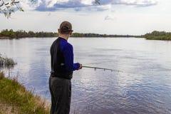 Pesci del pescatore che filano sulla sponda del fiume immagine stock libera da diritti