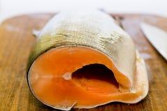 Pesci di color salmone freschi con la lama sullo scrittorio di cottura di legno Immagini Stock Libere da Diritti