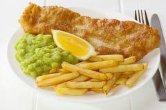 Pesci e chip con i piselli pastosi Fotografie Stock