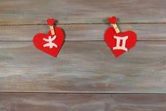 Pesci e gemelli segni dello zodiaco e del cuore Backgrou di legno Immagine Stock