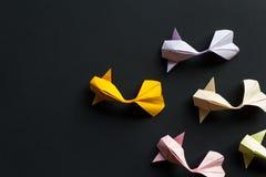 Pesci fatti a mano della carpa a specchi dell'oro di origami del mestiere di carta su fondo nero Vista superiore, modello immagini stock libere da diritti