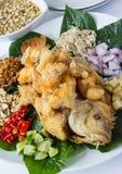 Pesci fritti nel grasso bollente con l'insalata dell'erba Immagini Stock