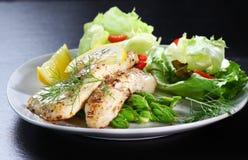 Pesci su asparago verde con insalata Fotografia Stock