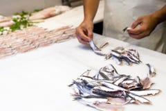 Pescivendolo che prepara pesce per la vendita al mercato ittico Fotografia Stock