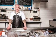 Pescivendolo dietro il suo contatore del pesce, Regno Unito Fotografia Stock