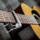 Pescoço da guitarra acústica com um capo Fotografia de Stock