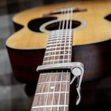 Pescoço da guitarra acústica com um capo Imagens de Stock Royalty Free
