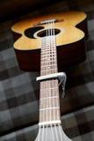 Pescoço da guitarra acústica com um capo Foto de Stock