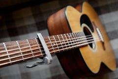 Pescoço da guitarra acústica com um capo Fotografia de Stock Royalty Free