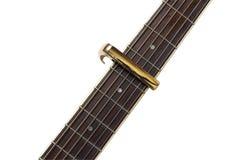 Pescoço da guitarra elétrica com um capo isolado no fundo branco Fotografia de Stock