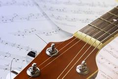 Pescoço da guitarra no fundo das folhas com notas imagens de stock