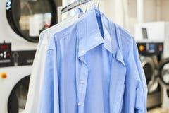 Pese camisas limpas em ganchos fotografia de stock royalty free