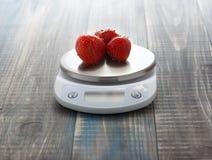 Pese das morangos em escalas digitais da cozinha imagem de stock