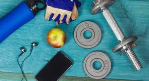 Pesez les plats, les gants et le smartphone sur le fond en bois Photographie stock