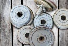 Pesi della testa di legno dell'attrezzatura di forma fisica su vecchio fondo di legno Fotografia Stock