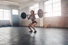Pesi di sollevamento dell'atleta femminile di forma fisica in palestra Fotografie Stock Libere da Diritti